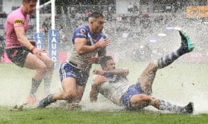 Nick Cotric and Corey Allan of the Bulldogs dive for the ball in the wet at Bankwest Stadium