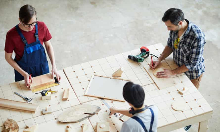 Making wooden detail for interior designDirectly above view of busy concentrated carpenters standing at table and making wooden detail for interior design, men drawing outline