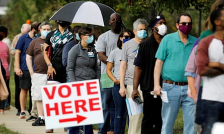 Voters wait in line on the first day of in-person early voting in Durham, North Carolina.