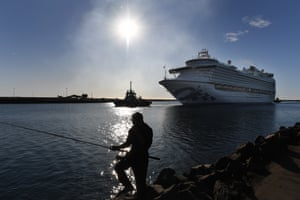Wollongong, Australia A fisherman wearing a face mask looks on as the Ruby Princess, with only crew onboard, docks at Port Kembla. A criminal investigation will be launched into how the cruise line operator Carnival Australia was allowed to disembark Ruby Princess passengers