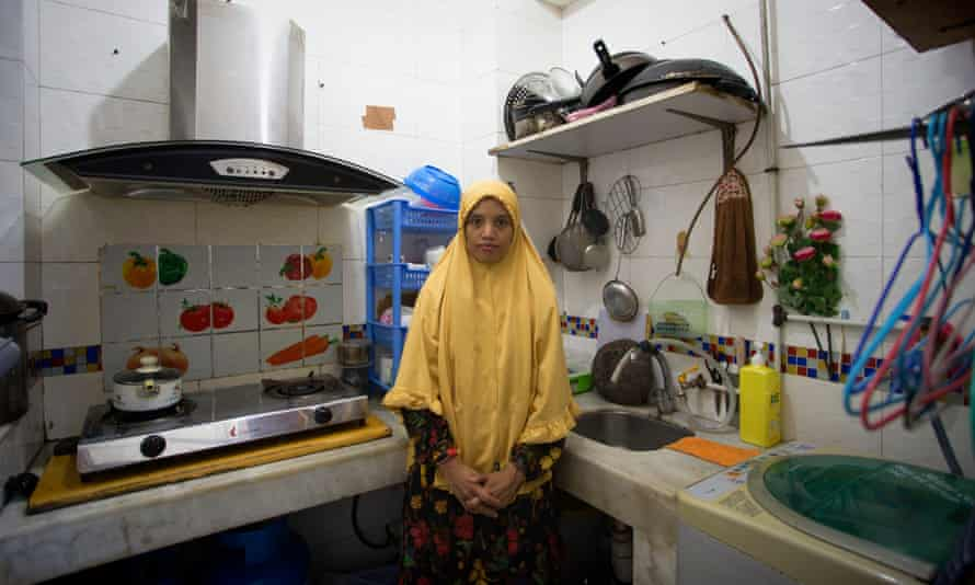 Ratna Khaleesy, migrant worker, stands in kitchen at home shared by 11 others, Macau