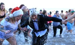 People run in to the sea in Cromer, Norfolk, UK