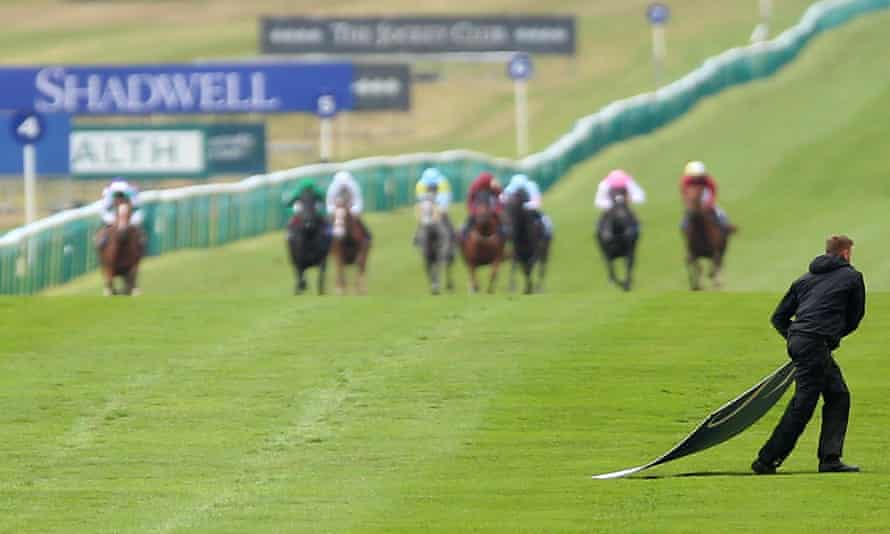 A member of groundstaff removes a piece of advertising hoarding that had blown onto the course at Newmarket.