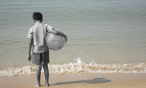Boy standing with facing sea holding a ball