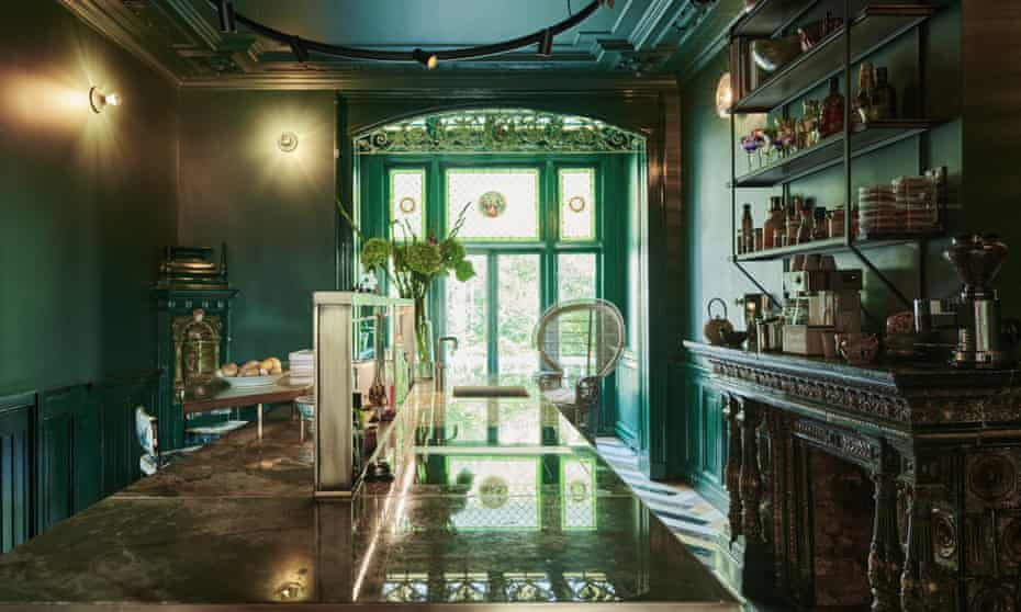 Rich greens, stained glass and floor-to-ceiling windows in the kitchen, which features 30 different types of marble and an onyx worktop.