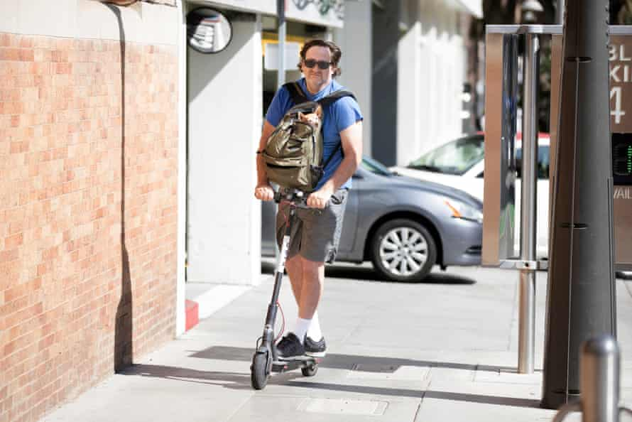 A Bird scooter rider travels with his dog in Santa Monica, California