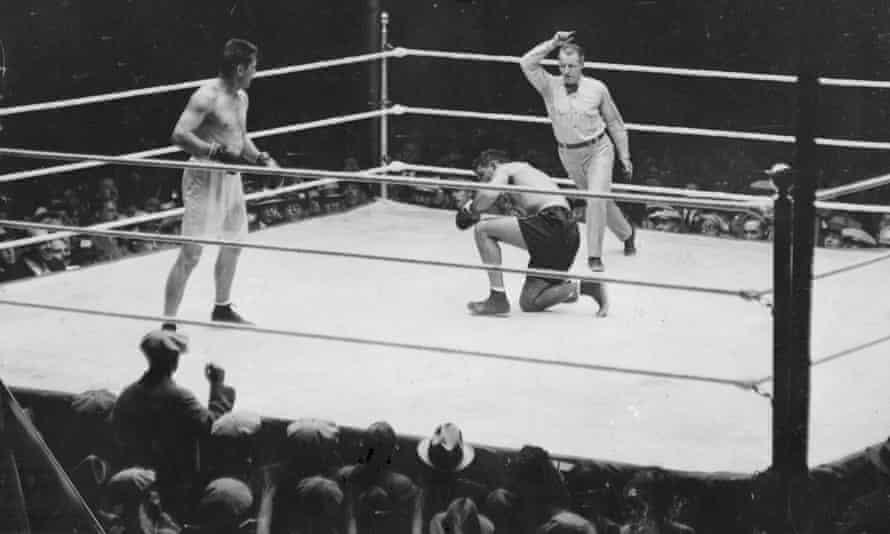Gene Tunney (L) looks on after he knocks down Jack Dempsey during the fight in Chicago on 22 September 1927. Gene Tunney won the contest.
