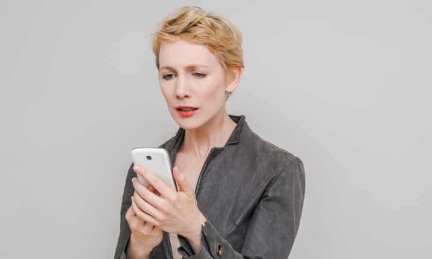 Portrait of distraught blond woman looking at her smartphone in front of grey background