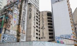 Graffiti displayed on a wall reads 'Doria thief' and 'Doria, Pixação is art' in São Paulo.