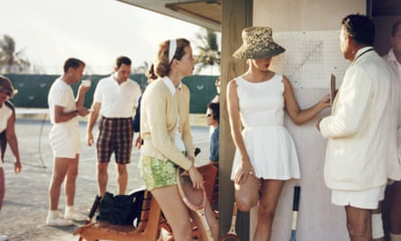 Two women stand talking to a man on the edge of a tennis court in the Bahamas, circa 1957. Behind the main group stand a second group of people talking. (Photo by Slim Aarons/Getty Images)