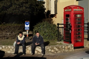Spanish workers sit next to a traditional red telephone box in Gibraltar, W.