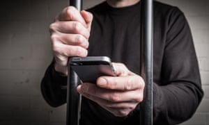 A prisoner in prison using a mobile phone behind bars in a cell.
