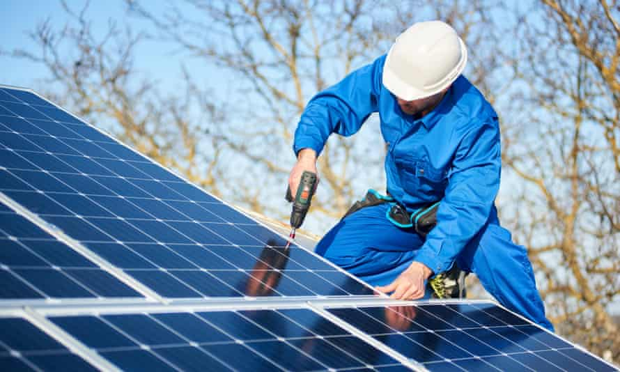 A workman installing a solar panel