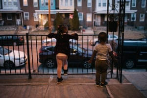 Cissy, four, left, and Aly, two, wait for their dad at their home in Philadelphia. Both were found to have lead poisoning from paint.
