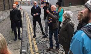 Derek McGuire, wearing scarf, leads a tour group through Dublin's LIberties neighbourhood