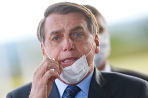 13 May: Bolsonaro adjusts his mask as he leaves his official residence, Alvorada Palace in Brasília.