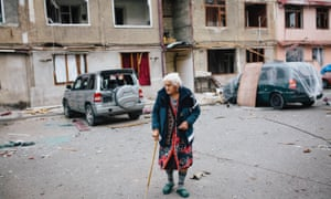 An elderly woman leaves her apartment during a lull in shelling in Stebanakert.