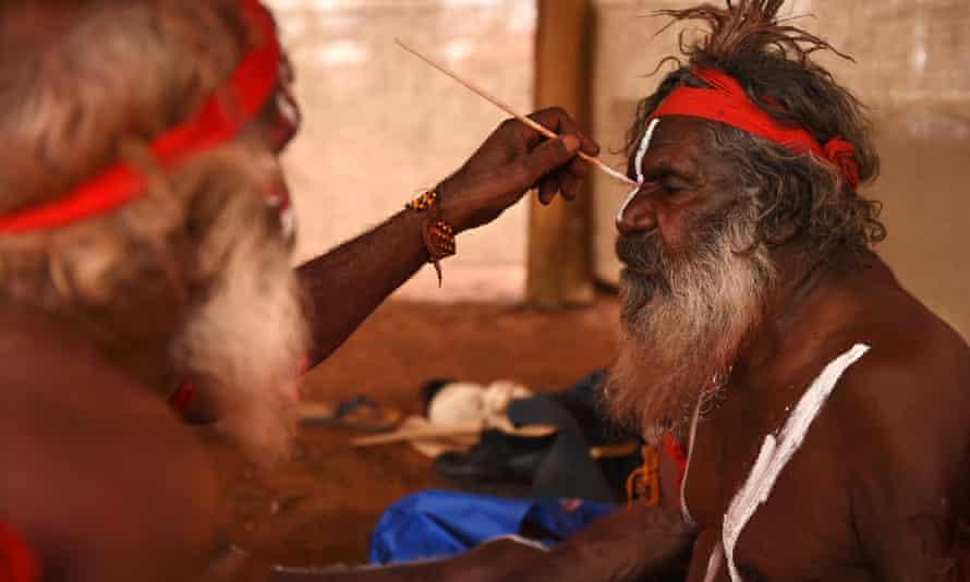 An Indigenous Australian man paints a fellow elder
