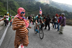 Spectators cheer as cyclists ride uphill during the fourth stage of the Tour de Langkawi in Malaysia