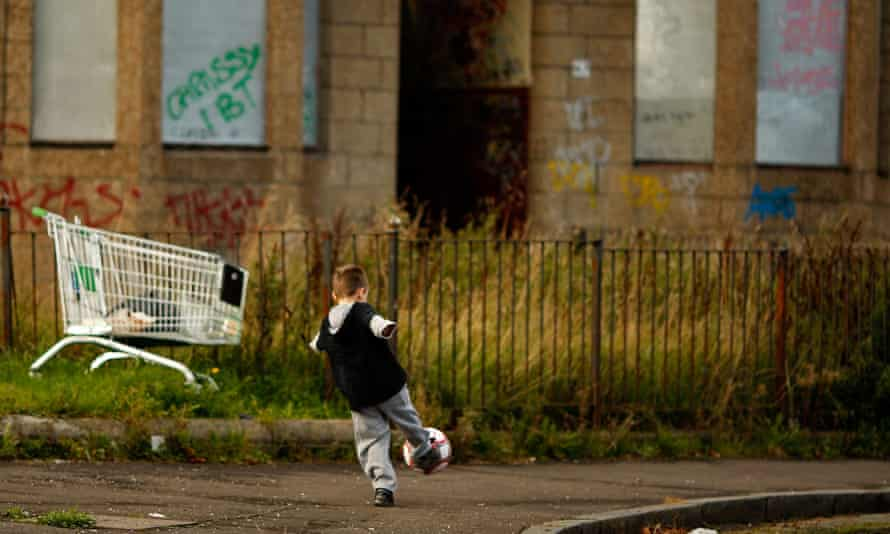 A young boy plays football in a run down street
