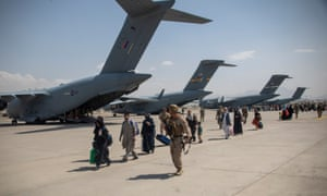 UK soldier leading evacuees to planes for evacuation from Kabul.