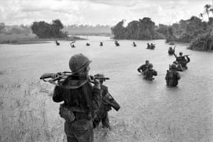 US paratroopers of the 2nd Battalion, 173rd Airborne Brigade, hold their automatic weapons above water as they cross a river in the rain during a search for Viet Cong positions in the jungle area of Ben Cat, September 25, 1965