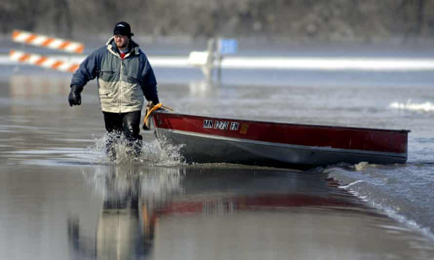 Jared Bakko hauls a boat down a flooded road after taking supplies to his grandmother as the Red River flood waters began to recede just south of Moorhead, Minnesota, USA, 28 March, 2009. EPA/CRAIG LASSIG