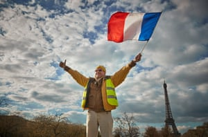 Paris, FranceA Gilet Jaune or Yellow Vest waves the French Tricolor flag during a demonstration near the Eiffel Tower as part of the National General Strike, organised by five French Unions in a demand for tax reforms and a rise in wages