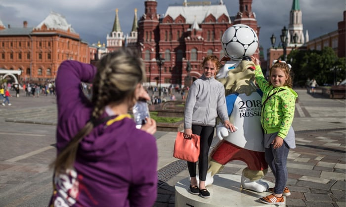 Two girls pose for a photograph by a figure of Wolf Zabivaka, the official mascot of the 2018 World Cup, in Moscow's Manezhnaya Square