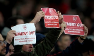Arsenal fans hold anti Unai Emery signs reading Emery out.