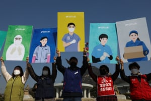 South KoreaActivists hold up portraits depicting the roles of female workers during a rally in Seoul. The protesters called for an equal society free from institutional discrimination