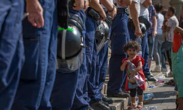 A young girl walks in front of Hungarian police officers prevent people from entering a central Budapest train station.