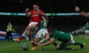Wales' Josh Adams (left) is tackled by Ireland's Jamison Gibson Park (centre) as Ireland's Peter O'Mahony attempts to ground the ball .