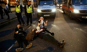 Students lie in the road after the demonstration to protest against cuts to grants in central London.