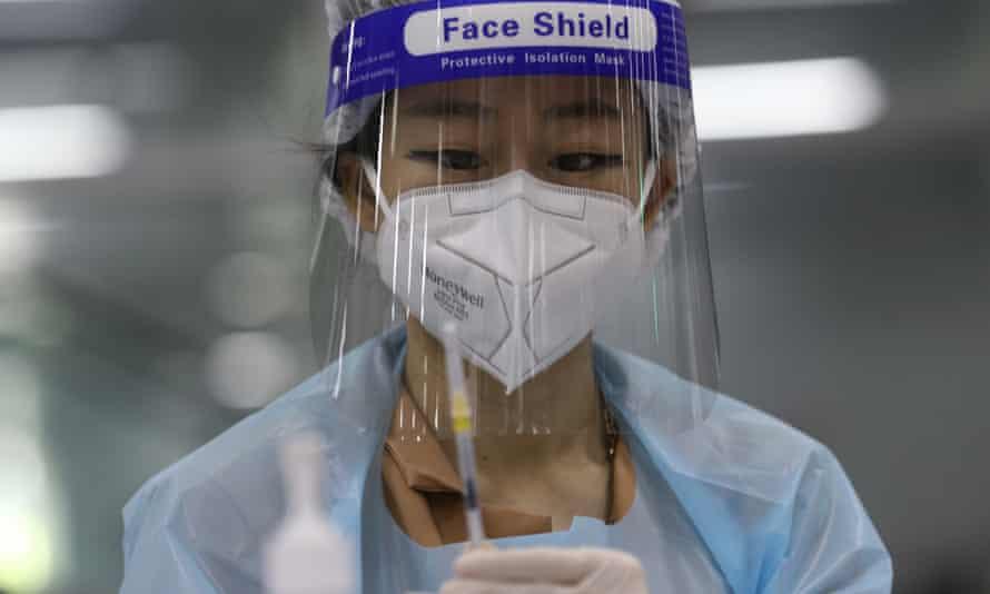 A health official prepares a dose of AstraZenca COVID-19 vaccine at a vaccination center
