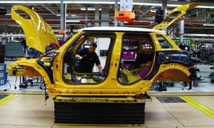 An employee installs a wiring loom into a Mini car as it travels along the assembly line at the BMW plant in Oxford