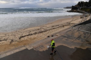 A worker sprays sand off the boardwalk at Sydney's Coogee beach