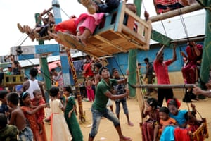 A man pulls a human-powered ferris wheel in the Kutupalong refugee camp, in Cox's Bazar, Bangladesh.