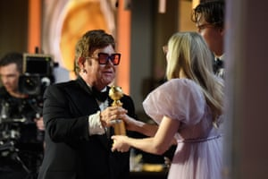 Sir Elton John accepting the award for best original song from Ansel Elgort and Dakota Fanning