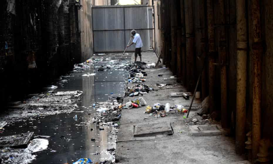 A man tries to clear the sewage in a lane in Mahul.