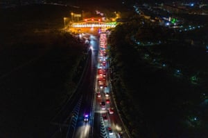 Cars queue at a highway toll station as they prepare to leave the city