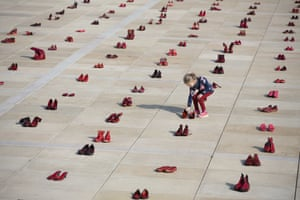 Hundreds of pairs of red shoes are displayed as a protest against violence towards women at Habima Square in Tel Aviv.