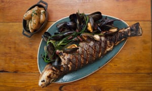 A whole crispy skinned sea bass with the head and tail hanging over the ends of the blue plate, mussels by the side and a small bowl of buttered new potatoes