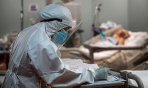 A nurse writes notes as a patient lies in bed in the intensive care unit for Covid-19 patients at the Casal Palocco Clinical Institute in Rome.