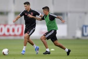 Cristiano Ronaldo and Joao Cancelo compete during training.
