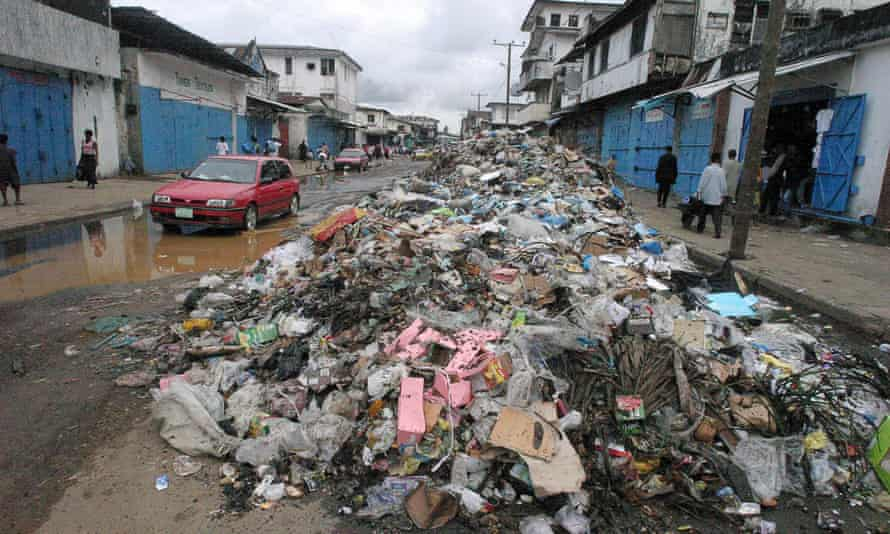 Liberians pass rubbish dumped in the streets of the capital, Monrovia.