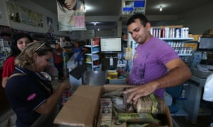 A man counts a bundle of bolivares, the currency of Venezuela, in the city of Pacaraima, where Venezuelans come to buy food and commodities scarce in their country.