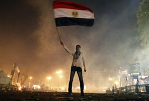 An Egyptian protester waves his national flag as he is surrounded by tear gas fired by riot police in Cairo's Tahrir Square on 25 January 2013.