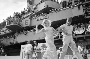 Actor Carroll Baker snaps her fingers at sailors cheering from the bridge as Bob Hope leads her across the stage on the flight deck of the USS Ticonderoga, December 1965