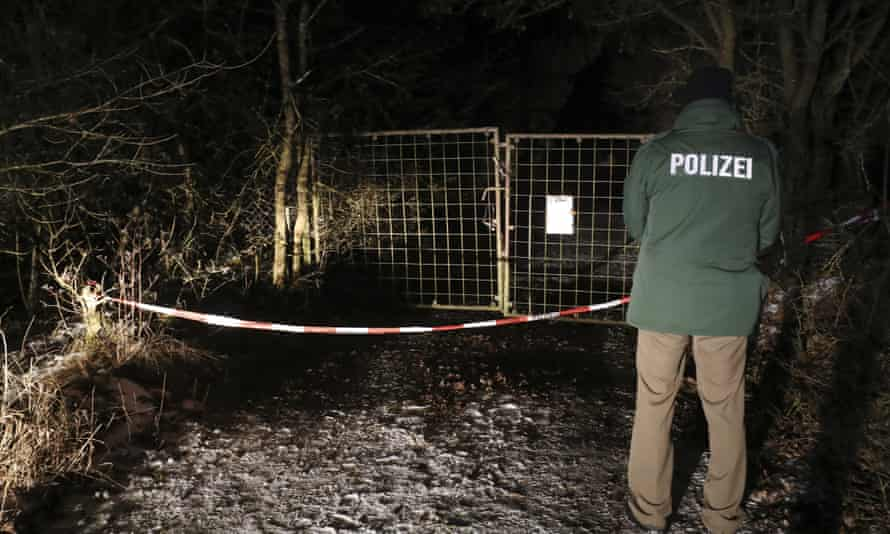 A police officer outside a property in Arnstein, Germany. Police say the bodies of six teenagers were found dead in a garden house.